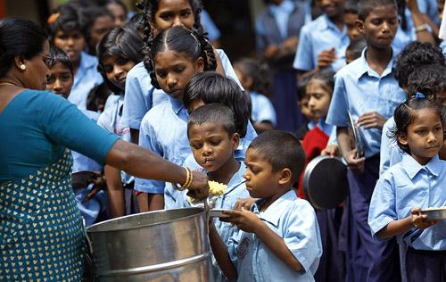 Фото. Индийский школьный учитель выдает еду школьникам