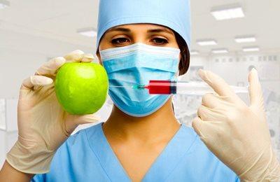 Фото. Врач делает укол яблоку
