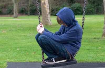 Фото. Мальчик сидит на качели и грустит
