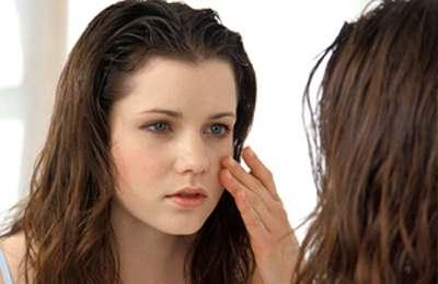 Фото. Девушка смотрит в зеркале свое лицо