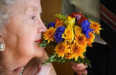 Пожилая женщина нюхает цветы