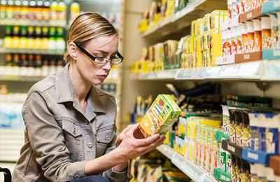 женщина смотрит на маркировку продуктов питания
