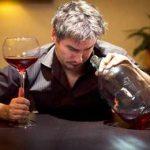 мужчина заглядывает в бутылку с вином