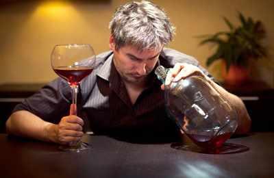 пьянй мужчина с бутылкой и бокалом вина