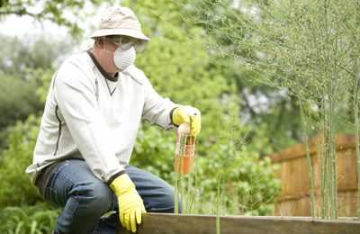 садовник опрыскивает глифосатом