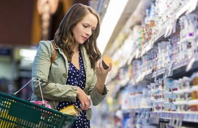 женщина читает этикетку на продуктах в магазине